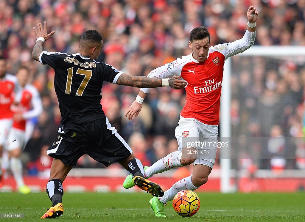 Leicester City's English defender Danny Simpson (L) vies with Arsenal's German midfielder Mesut Ozil during the English Premier League football match between Arsenal and Leicester at the Emirates Stadium in London on February 14, 2016. / AFP / GLYN KIRK / RESTRICTED TO EDITORIAL USE. No use with unauthorized audio, video, data, fixture lists, club/league logos or 'live' services. Online in-match use limited to 75 images, no video emulation. No use in betting, games or single club/league/player publications. /