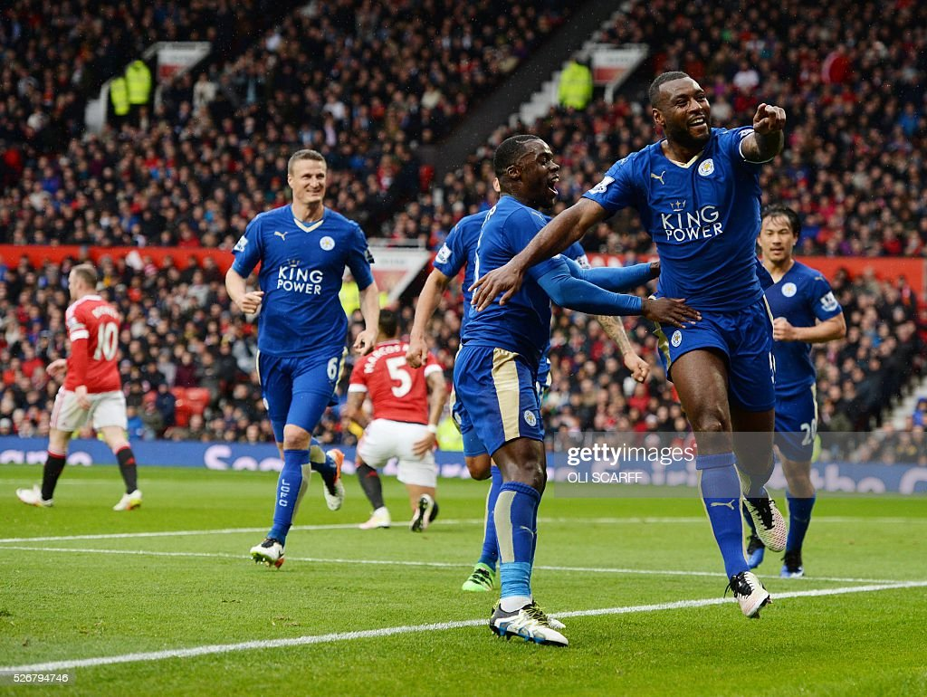 Leicester City's English defender Wes Morgan (R) celebrates scoring the equalising 1-1 goal with Leicester City's Ghanaian striker Jeff Schlupp (2R) during the English Premier League football match between Manchester United and Leicester City at Old Trafford in Manchester, north west England, on May 1, 2016. / AFP / OLI SCARFF / RESTRICTED TO EDITORIAL USE. No use with unauthorized audio, video, data, fixture lists, club/league logos or 'live' services. Online in-match use limited to 75 images, no video emulation. No use in betting, games or single club/league/player publications. /