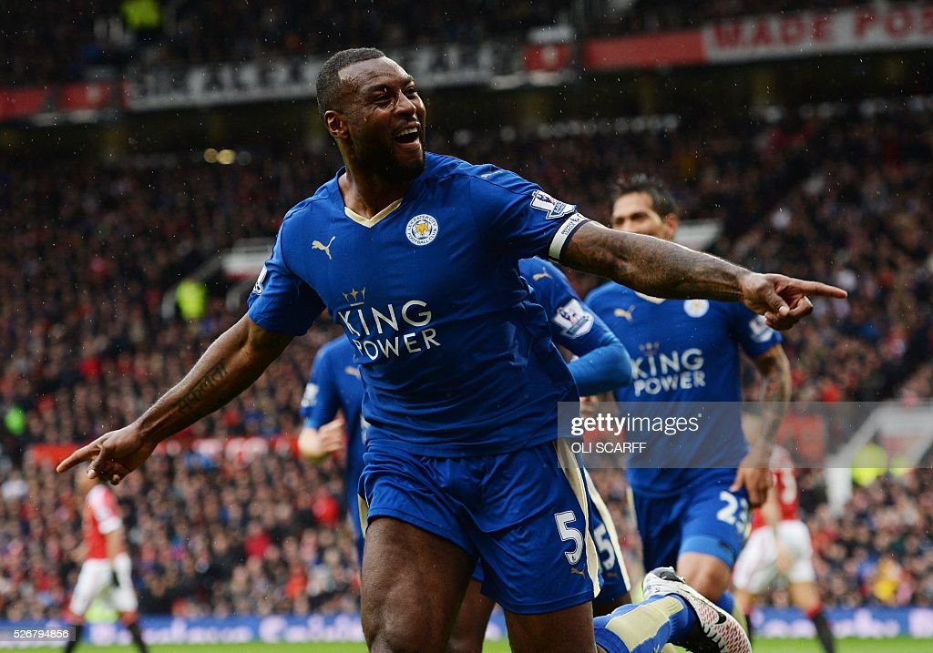 Leicester City's English defender Wes Morgan celebrates scoring the equalising 1-1 goal with Leicester City's Ghanaian striker Jeff Schlupp (2R) during the English Premier League football match between Manchester United and Leicester City at Old Trafford in Manchester, north west England, on May 1, 2016. / AFP / OLI SCARFF / RESTRICTED TO EDITORIAL USE. No use with unauthorized audio, video, data, fixture lists, club/league logos or 'live' services. Online in-match use limited to 75 images, no video emulation. No use in betting, games or single club/league/player publications. /