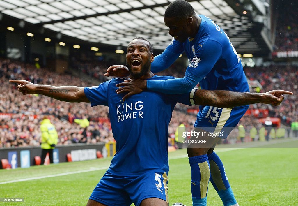 Leicester City's English defender Wes Morgan (L) celebrates scoring the equalising 1-1 goal with Leicester City's Ghanaian striker Jeff Schlupp (R) during the English Premier League football match between Manchester United and Leicester City at Old Trafford in Manchester, north west England, on May 1, 2016. / AFP / OLI SCARFF / RESTRICTED TO EDITORIAL USE. No use with unauthorized audio, video, data, fixture lists, club/league logos or 'live' services. Online in-match use limited to 75 images, no video emulation. No use in betting, games or single club/league/player publications. /
