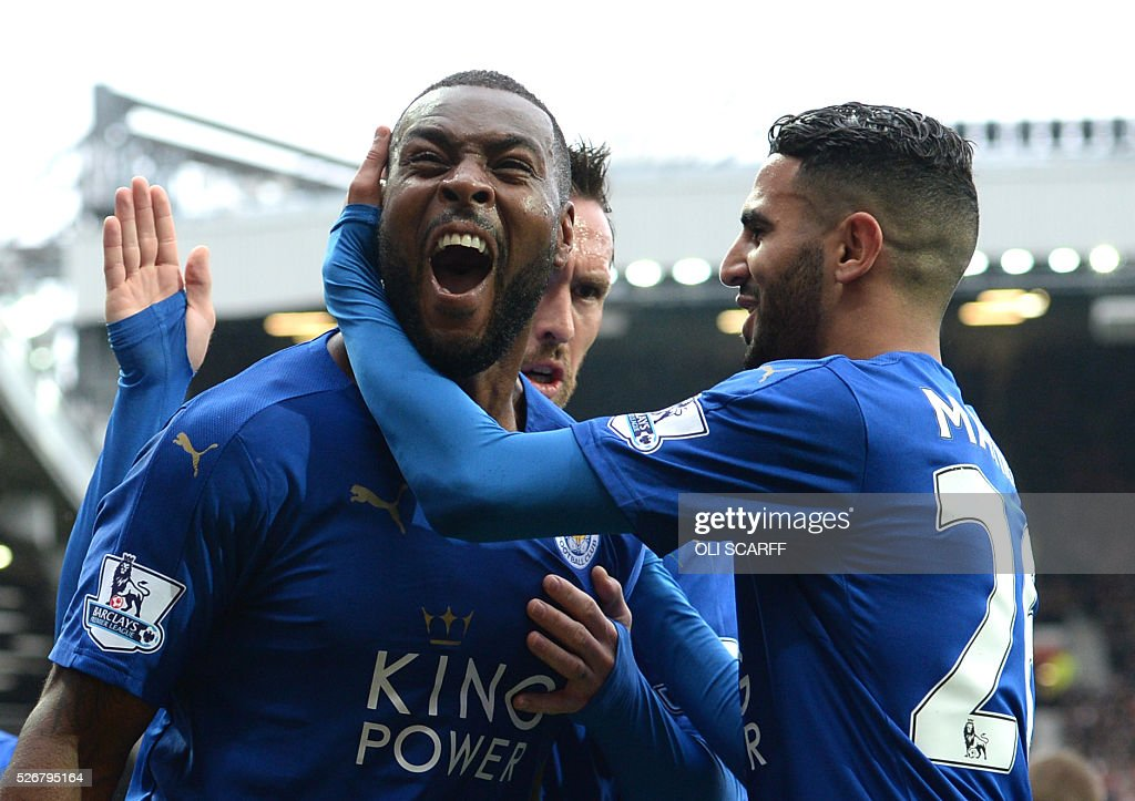 Leicester City's English defender Wes Morgan (L) celebrates scoring the equalising 1-1 goal with Leicester City's Algerian midfielder Riyad Mahrez (R) during the English Premier League football match between Manchester United and Leicester City at Old Trafford in Manchester, north west England, on May 1, 2016. / AFP / OLI SCARFF / RESTRICTED TO EDITORIAL USE. No use with unauthorized audio, video, data, fixture lists, club/league logos or 'live' services. Online in-match use limited to 75 images, no video emulation. No use in betting, games or single club/league/player publications. /