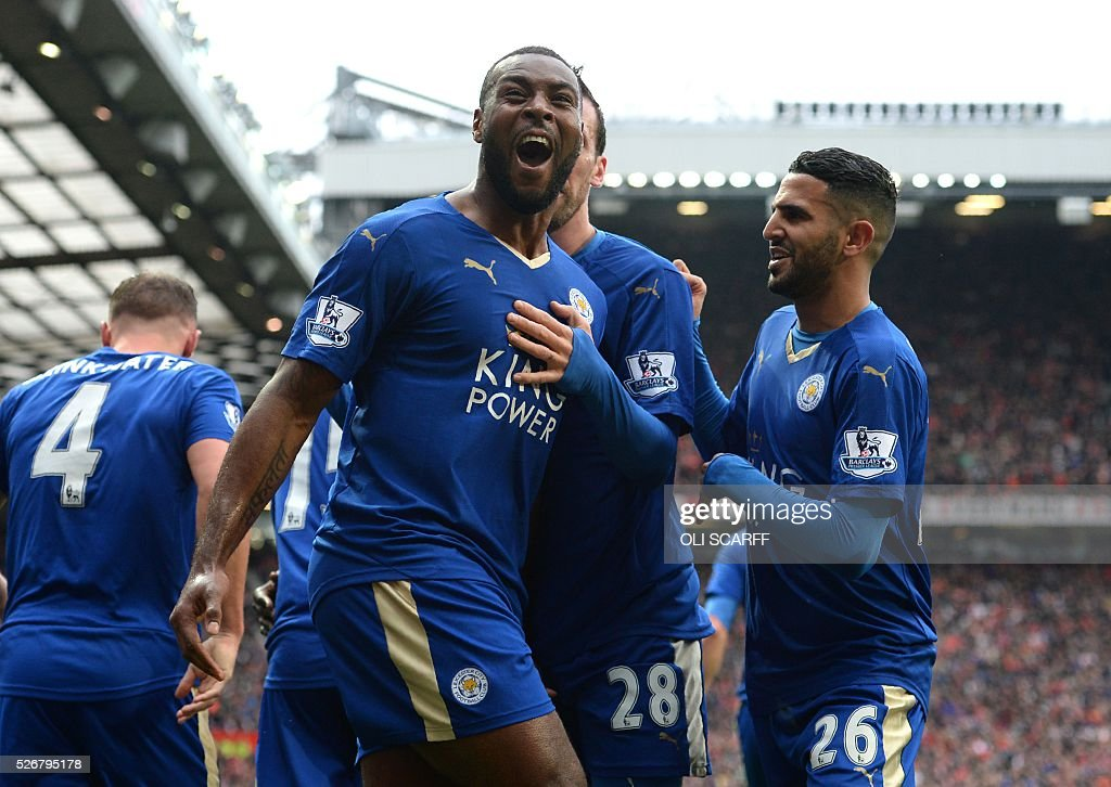 Leicester City's English defender Wes Morgan (C) celebrates scoring the equalising 1-1 goal with Leicester City's Algerian midfielder Riyad Mahrez (R) during the English Premier League football match between Manchester United and Leicester City at Old Trafford in Manchester, north west England, on May 1, 2016. / AFP / OLI SCARFF / RESTRICTED TO EDITORIAL USE. No use with unauthorized audio, video, data, fixture lists, club/league logos or 'live' services. Online in-match use limited to 75 images, no video emulation. No use in betting, games or single club/league/player publications. /