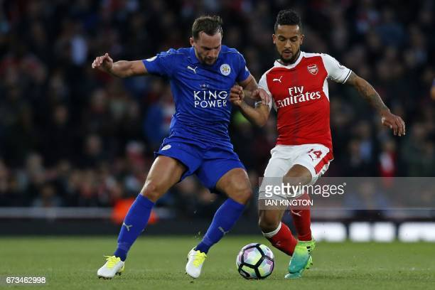 Leicester City's English midfielder Danny Drinkwater vies with Arsenal's English midfielder Theo Walcott during the English Premier League football...