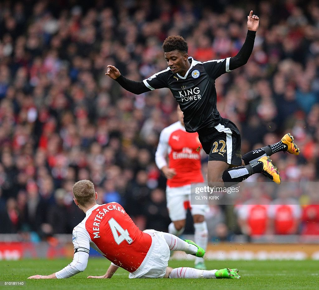 Leicester City's English midfielder Demarai Gray (R) jumps a challenge from Arsenal's German defender Per Mertesacker during the English Premier League football match between Arsenal and Leicester at the Emirates Stadium in London on February 14, 2016. / AFP / GLYN KIRK / RESTRICTED TO EDITORIAL USE. No use with unauthorized audio, video, data, fixture lists, club/league logos or 'live' services. Online in-match use limited to 75 images, no video emulation. No use in betting, games or single club/league/player publications. /