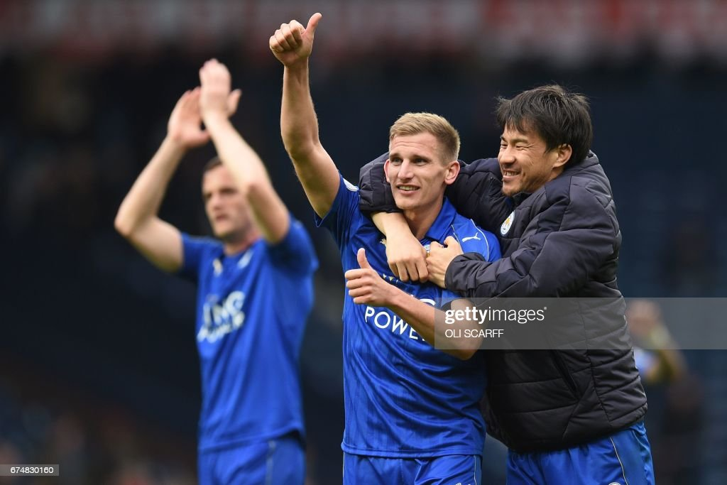 Leicester City's English midfielder Marc Albrighton (C) and Leicester City's Japanese striker Shinji Okazaki celebrate on the pitch after the English Premier League football match between West Bromwich Albion and Leicester City at The Hawthorns stadium in West Bromwich, central England, on April 29, 2017. Leicester won the game 1-0. / AFP PHOTO / Oli SCARFF / RESTRICTED TO EDITORIAL USE. No use with unauthorized audio, video, data, fixture lists, club/league logos or 'live' services. Online in-match use limited to 75 images, no video emulation. No use in betting, games or single club/league/player publications. /