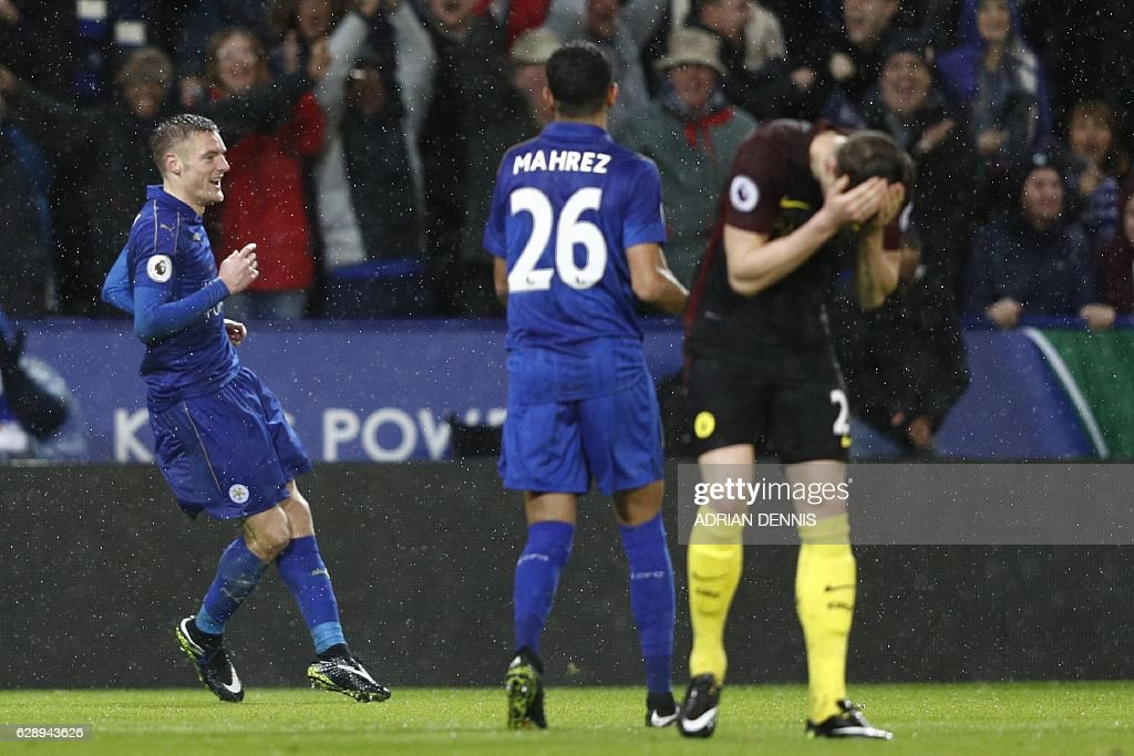 Leicester City's English striker Jamie Vardy (L) celebrates after scoring his third goal, their fourth as Manchester City's English defender John Stones (R) reacts during the English Premier League football match between Leicester City and Manchester City at King Power Stadium in Leicester, central England on December 10, 2016. / AFP / Adrian DENNIS / RESTRICTED TO EDITORIAL USE. No use with unauthorized audio, video, data, fixture lists, club/league logos or 'live' services. Online in-match use limited to 75 images, no video emulation. No use in betting, games or single club/league/player publications. /