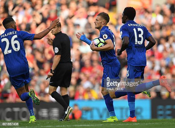 Leicester City's English striker Jamie Vardy celebrates with Leicester City's Algerian midfielder Riyad Mahrez after scoring their first goal during...