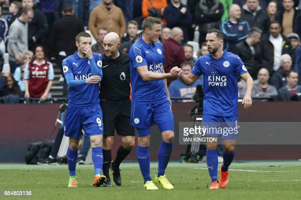 Leicester City's English striker Jamie Vardy speaks to the referee after scoring during the English Premier League football match between West Ham...