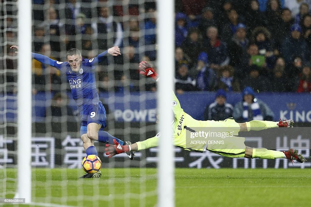 Leicester City's English striker Jamie Vardy (L) takes the ball around Manchester City's Chilean goalkeeper Claudio Bravo on his way to scoring his third goal, their fourth during the English Premier League football match between Leicester City and Manchester City at King Power Stadium in Leicester, central England on December 10, 2016. Leicester won the game 4-2. / AFP / Adrian DENNIS / RESTRICTED TO EDITORIAL USE. No use with unauthorized audio, video, data, fixture lists, club/league logos or 'live' services. Online in-match use limited to 75 images, no video emulation. No use in betting, games or single club/league/player publications. /