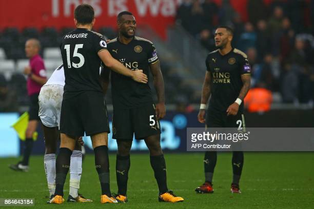 Leicester City's Englishborn Jamaican defender Wes Morgan and Leicester City's English defender Harry Maguire celebrate their win on the pitch after...