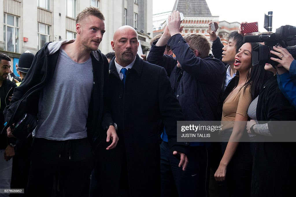 Leicester City's football player Jamie Vardy (L) is cheered by crowds of waiting fans as he arrives for lunch at an Italian Restraunt in the centre of Leicester on May 3, 2016, the day after Leicester City won the English Premier League title. Thousands celebrated and millions around the world watched in wonder as 5,000-1 underdogs Leicester City completed arguably the greatest fairytale in sporting history by becoming English Premier League champions. / AFP / JUSTIN
