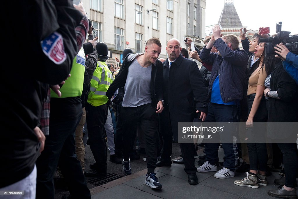 Leicester City's football player Jamie Vardy (C) is cheered by crowds of waiting fans as he arrives for lunch at an Italian Restraunt in the centre of Leicester on May 3, 2016, the day after Leicester City won the English Premier League title. Thousands celebrated and millions around the world watched in wonder as 5,000-1 underdogs Leicester City completed arguably the greatest fairytale in sporting history by becoming English Premier League champions. / AFP / JUSTIN