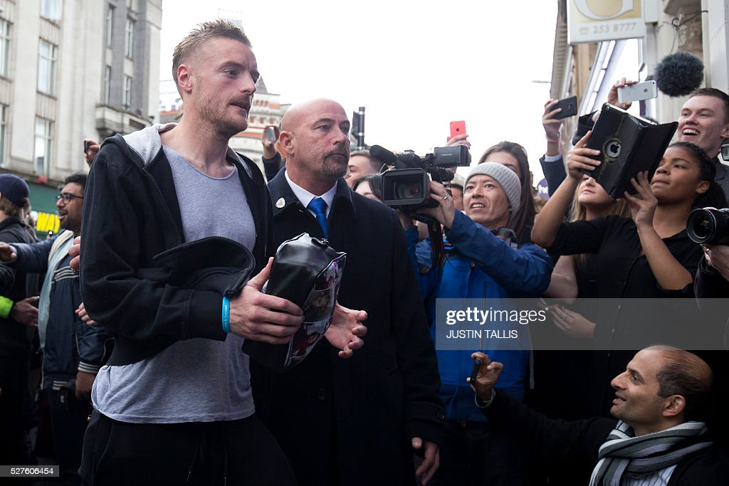 Leicester City's football player Jamie Vardy (L) is cheered by crowds of waiting fans as he arrives for lunch at an Italian restaurant in the centre of Leicester on May 3, 2016, the day after Leicester City won the English Premier League title. Thousands celebrated and millions around the world watched in wonder as 5,000-1 underdogs Leicester City completed arguably the greatest fairytale in sporting history by becoming English Premier League champions. / AFP / JUSTIN