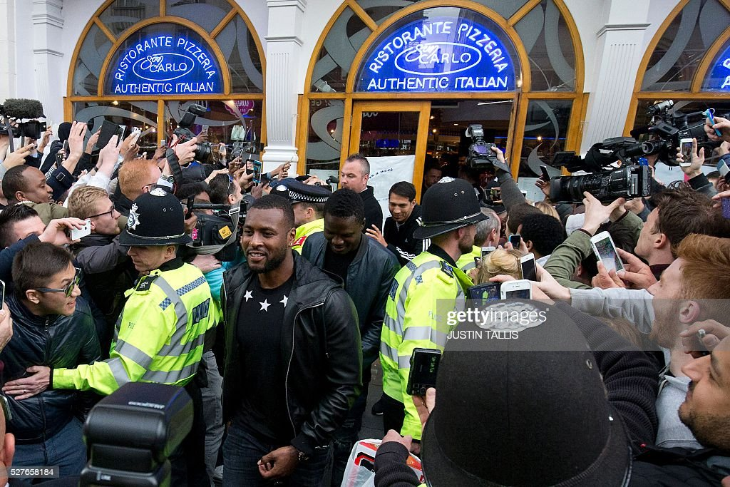 Leicester City's footballer and captain Wes Morgan (C) is mobbed by fans as he leaves an Italian restaurant after having lunch with team-mates in the centre of Leicester on May 3, 2016, the day after winning the English Premier League title. Thousands celebrated and millions around the world watched in wonder as 5,000-1 underdogs Leicester City completed arguably the greatest fairytale in sporting history by becoming English Premier League champions. / AFP / JUSTIN