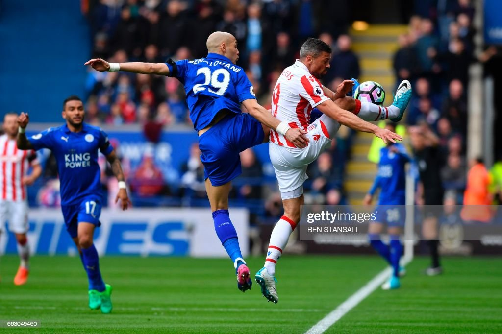 TOPSHOT - Leicester City's French defender Yohan Benalouane (C) vies with Stoke City's English-born Irish striker Jonathan Walters (R) during the English Premier League football match between Leicester City and Stoke City at King Power Stadium in Leicester, central England on April 1, 2017. / AFP PHOTO / Ben STANSALL / RESTRICTED TO EDITORIAL USE. No use with unauthorized audio, video, data, fixture lists, club/league logos or 'live' services. Online in-match use limited to 75 images, no video emulation. No use in betting, games or single club/league/player publications. /