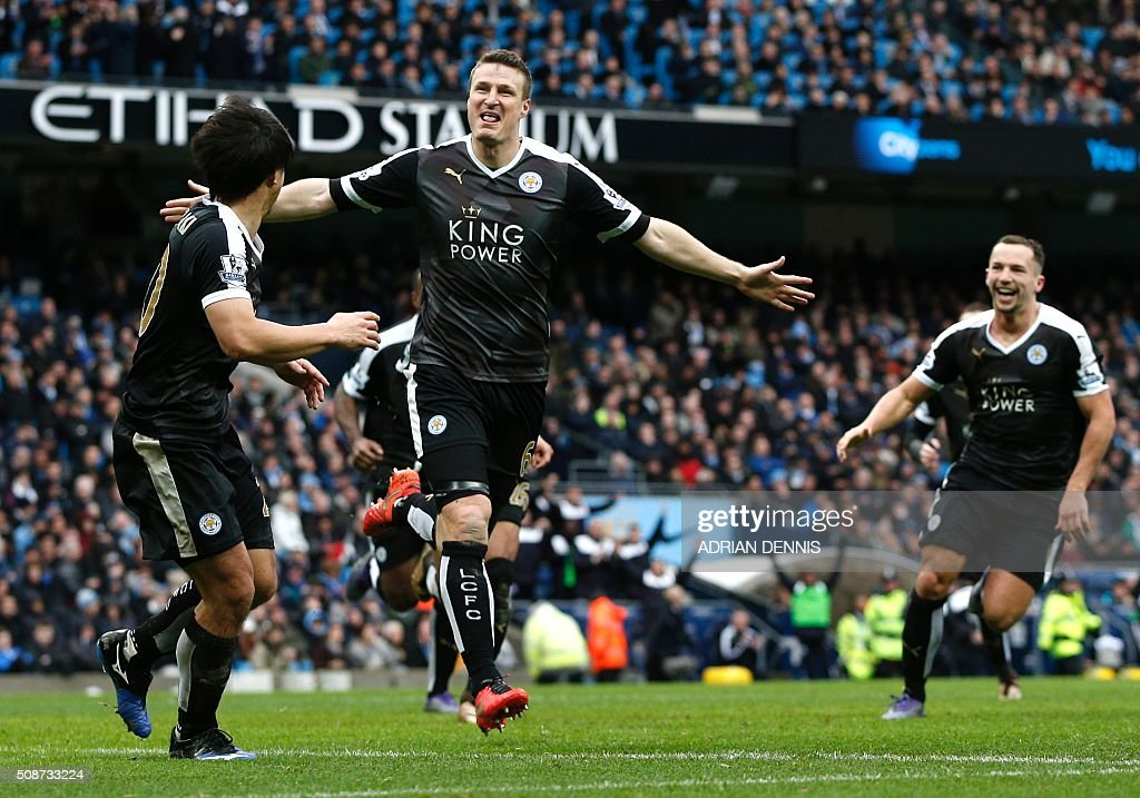 Leicester City's German defender Robert Huth (C) celebrates scoring his team's third goal with Leicester City's Japanese striker Shinji Okazaki (L) during the English Premier League football match between Manchester City and Leicester City at the Etihad Stadium in Manchester, north west England, on February 6, 2016. / AFP / ADRIAN DENNIS / RESTRICTED TO EDITORIAL USE. No use with unauthorized audio, video, data, fixture lists, club/league logos or 'live' services. Online in-match use limited to 75 images, no video emulation. No use in betting, games or single club/league/player publications. /