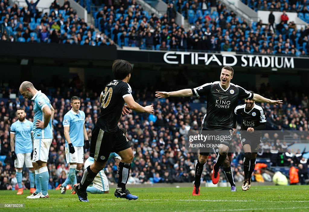 Leicester City's German defender Robert Huth (R) celebrates scoring his team's third goal with Leicester City's Japanese striker Shinji Okazaki (C) during the English Premier League football match between Manchester City and Leicester City at the Etihad Stadium in Manchester, north west England, on February 6, 2016. / AFP / ADRIAN DENNIS / RESTRICTED TO EDITORIAL USE. No use with unauthorized audio, video, data, fixture lists, club/league logos or 'live' services. Online in-match use limited to 75 images, no video emulation. No use in betting, games or single club/league/player publications. /