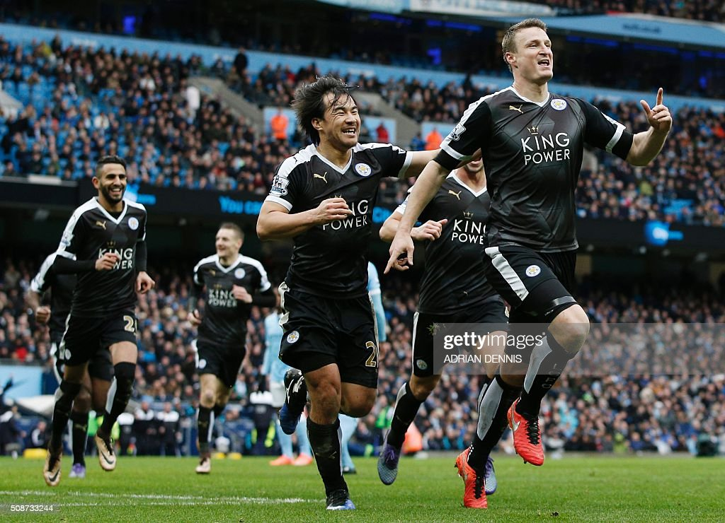 Leicester City's German defender Robert Huth (R) celebrates scoring his team's third goal with Leicester City's Japanese striker Shinji Okazaki (C) and Leicester City's Algerian midfielder Riyad Mahrez during the English Premier League football match between Manchester City and Leicester City at the Etihad Stadium in Manchester, north west England, on February 6, 2016. / AFP / ADRIAN DENNIS / RESTRICTED TO EDITORIAL USE. No use with unauthorized audio, video, data, fixture lists, club/league logos or 'live' services. Online in-match use limited to 75 images, no video emulation. No use in betting, games or single club/league/player publications. /