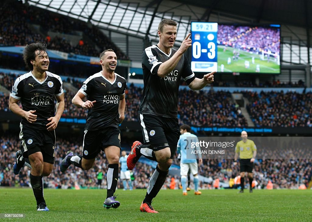 Leicester City's German defender Robert Huth (R) celebrates scoring his team's third goal with Leicester City's Japanese striker Shinji Okazaki (L) and Leicester City's Algerian midfielder Riyad Mahrez during the English Premier League football match between Manchester City and Leicester City at the Etihad Stadium in Manchester, north west England, on February 6, 2016. / AFP / ADRIAN DENNIS / RESTRICTED TO EDITORIAL USE. No use with unauthorized audio, video, data, fixture lists, club/league logos or 'live' services. Online in-match use limited to 75 images, no video emulation. No use in betting, games or single club/league/player publications. /