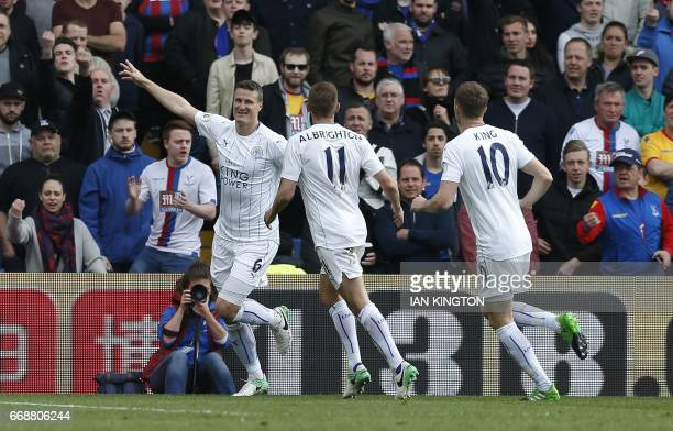 Leicester City's German defender Robert Huth celebrates with teammates after scoring the opening goal of the English Premier League football match...