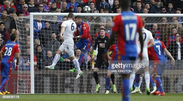 Leicester City's German defender Robert Huth jumps to head the opening goal past Crystal Palace's Welsh goalkeeper Wayne Hennessey during the English...