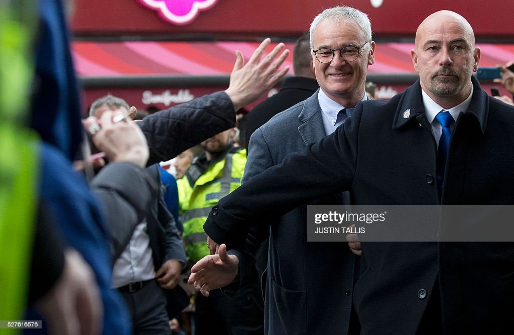 Leicester City's Italian football manager Claudio Ranieri (2R) is cheered by crowds of waiting fans as he arrives for lunch at an Italian restaurant in the centre of Leicester on May 3, 2016, the day after Leicester City won the English Premier League title. Thousands celebrated and millions around the world watched in wonder as 5,000-1 underdogs Leicester City completed arguably the greatest fairytale in sporting history by becoming English Premier League champions. / AFP / JUSTIN