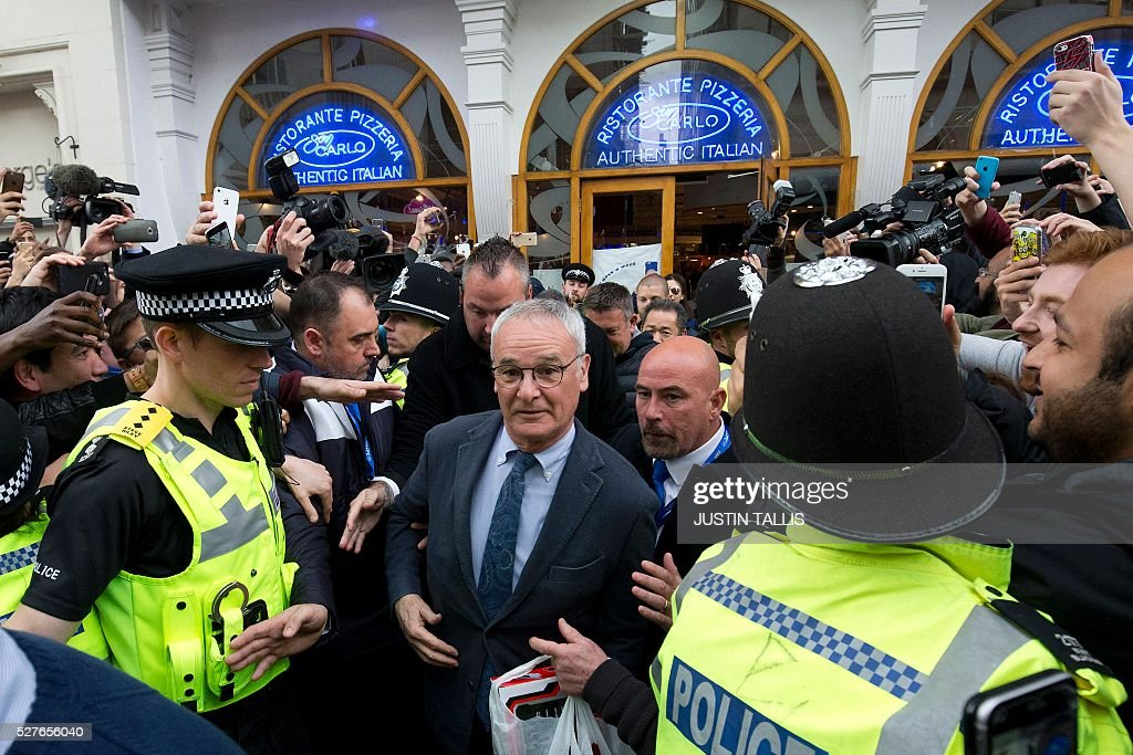 Leicester City's Italian football manager Claudio Ranieri (C) is mobbed by fans as he leaves an Italian restaurant after having lunch with team-mates in the centre of Leicester on May 3, 2016, the day after winning the English Premier League title. Thousands celebrated and millions around the world watched in wonder as 5,000-1 underdogs Leicester City completed arguably the greatest fairytale in sporting history by becoming English Premier League champions. / AFP / JUSTIN
