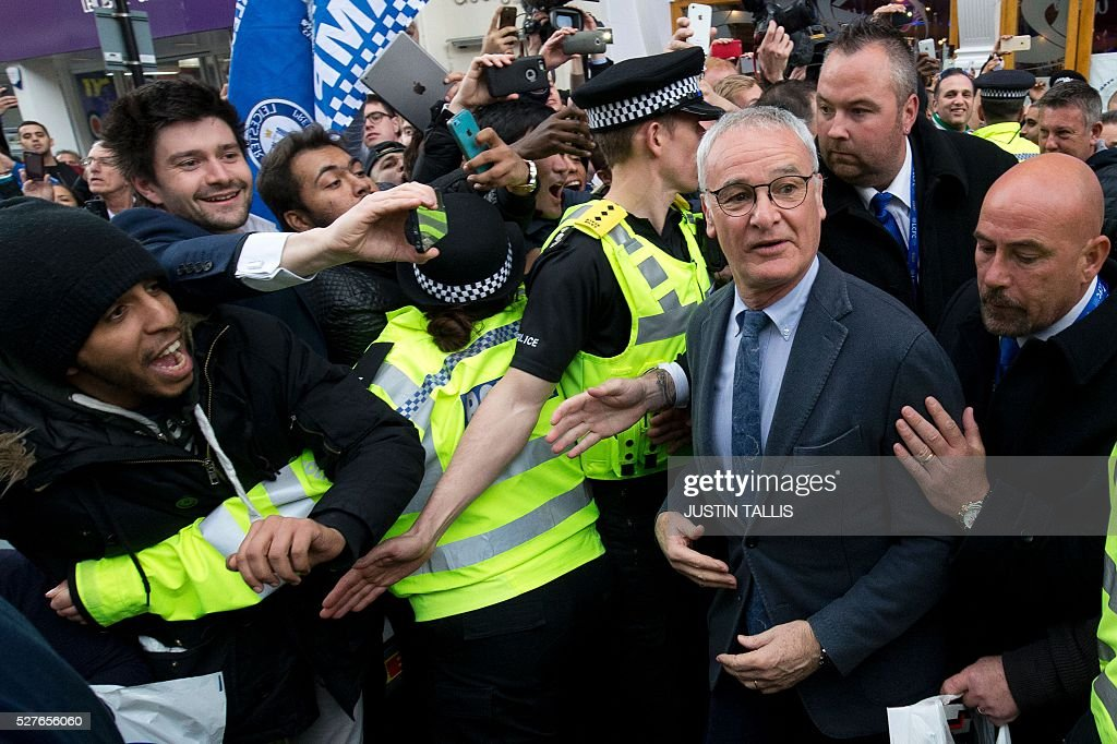 Leicester City's Italian football manager Claudio Ranieri (R) is mobbed by fans as he leaves an Italian restaurant after having lunch with team-mates in the centre of Leicester on May 3, 2016, the day after winning the English Premier League title. Thousands celebrated and millions around the world watched in wonder as 5,000-1 underdogs Leicester City completed arguably the greatest fairytale in sporting history by becoming English Premier League champions. / AFP / JUSTIN