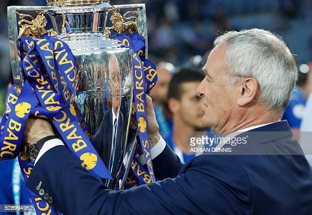 Leicester City's Italian manager Claudio Ranieri kisses the premier league trophy after winning the league and the English Premier League football...