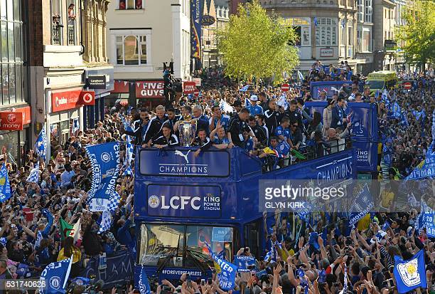 TOPSHOT Leicester City's Italian manager Claudio Ranieri stands with the Premier league trophy as the Leicester City team take part in an opentop bus...