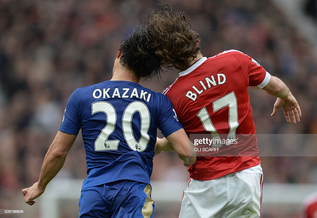 Leicester City's Japanese striker Shinji Okazaki (L) and Manchester United's Dutch midfielder Daley Blind (R) go for a high ball during the English Premier League football match between Manchester United and Leicester City at Old Trafford in Manchester, north west England, on May 1, 2016. / AFP / OLI SCARFF / RESTRICTED TO EDITORIAL USE. No use with unauthorized audio, video, data, fixture lists, club/league logos or 'live' services. Online in-match use limited to 75 images, no video emulation. No use in betting, games or single club/league/player publications. /