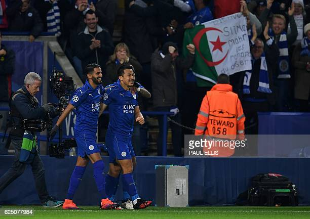 Leicester City's Japanese striker Shinji Okazaki celebrates scoring his team's first goal with Leicester City's Algerian midfielder Riyad Mahrez...