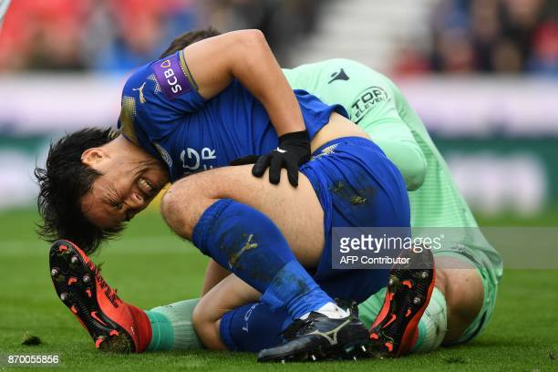 Leicester City's Japanese striker Shinji Okazaki reacts after hurting himself after a collision with Stoke City's English goalkeeper Jack Butland...