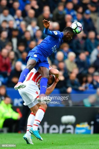 Leicester City's Nigerian midfielder Wilfred Ndidi beats Stoke City's Englishborn Irish striker Jonathan Walters to head the ball during the English...