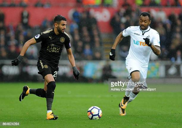 Leicester City's Riyad Mahrez vies for possession with Swansea City's Jordan Ayew during the Premier League match between Swansea City and Leicester...