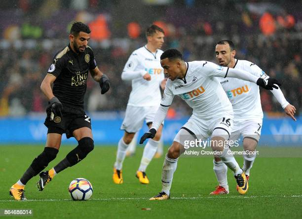 Leicester City's Riyad Mahrez vies for possession with Swansea City's Martin Olsson during the Premier League match between Swansea City and...