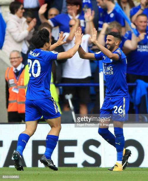 Leicester City's Shinji Okazaki celebrates scoring his side's first goal with teammate Riyad Mahrez during the Premier League match at the King Power...