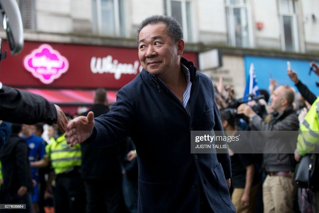 Leicester City's Thai owner and chairman Vichai Srivaddhanaprabha is cheered by crowds of waiting fans as he arrives for lunch at an Italian restaurant in the centre of Leicester on May 3, 2016, the day after Leicester City won the English Premier League title. Thousands celebrated and millions around the world watched in wonder as 5,000-1 underdogs Leicester City completed arguably the greatest fairytale in sporting history by becoming English Premier League champions. / AFP / JUSTIN