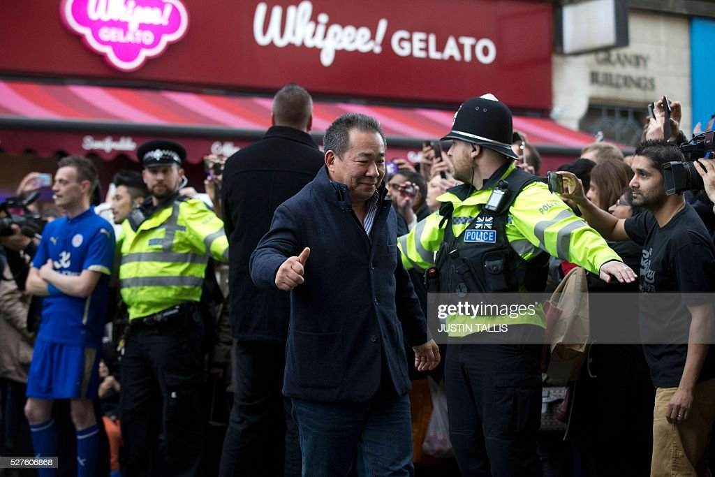 Leicester City's Thai owner and chairman Vichai Srivaddhanaprabha (C) is cheered by crowds of waiting fans as he arrives for lunch at an Italian restaurant in the centre of Leicester on May 3, 2016, the day after Leicester City won the English Premier League title. Thousands celebrated and millions around the world watched in wonder as 5,000-1 underdogs Leicester City completed arguably the greatest fairytale in sporting history by becoming English Premier League champions. / AFP / JUSTIN