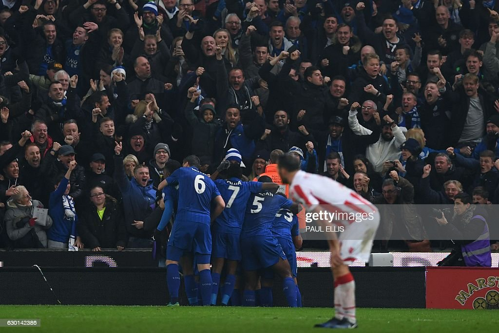 Leicester players mob Leicester City's Ghanaian midfielder Daniel Amartey after he scored his team's second goal during the English Premier League football match between Stoke City and Leicester City at the Bet365 Stadium in Stoke-on-Trent, central England on December 17, 2016. / AFP / Paul ELLIS / RESTRICTED TO EDITORIAL USE. No use with unauthorized audio, video, data, fixture lists, club/league logos or 'live' services. Online in-match use limited to 75 images, no video emulation. No use in betting, games or single club/league/player publications. /
