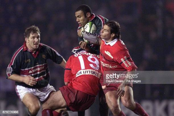 Leicester's Leon Lloyd is tackled by Beziers Frederic Gommard and Gonzaio Quesada during their Heineken Cup pool one match at Leicester's Welford...