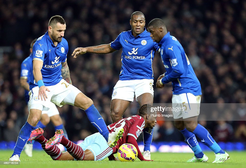Leicester's Marcin Wasilewski, Wes Morgan and Jeff Schlupp with West Ham's Diafra Sakho during the Barclays Premier League match between West Ham United and Leicester City at Boleyn Ground on December 20, 2014 in London, England.