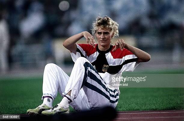 die Olympiasiegerin Heike Drechsler sitzt gestikulierend auf der Tartanbahn 1992