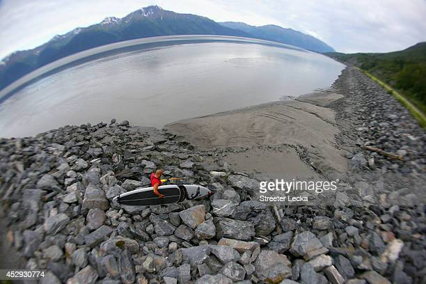 Leif Ramos walks down rocks to get into position to ride the Bore Tide at Turnagain Arm on July 15 2014 in Anchorage Alaska Alaska's most famous Bore...