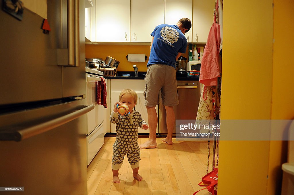 Leif Redmond, 36, prepares breakfast for his family while his youngest of two daughters, Mabel, 1, accompanies him at their family home in Logan Circle.
