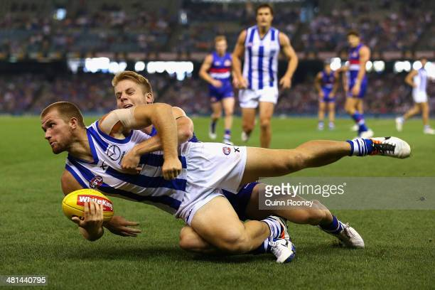 Leigh Adams of the Kangaroos handballs whilst being tackled by Lachie Hunter of the Bulldogs during the round two AFL match between the Western...