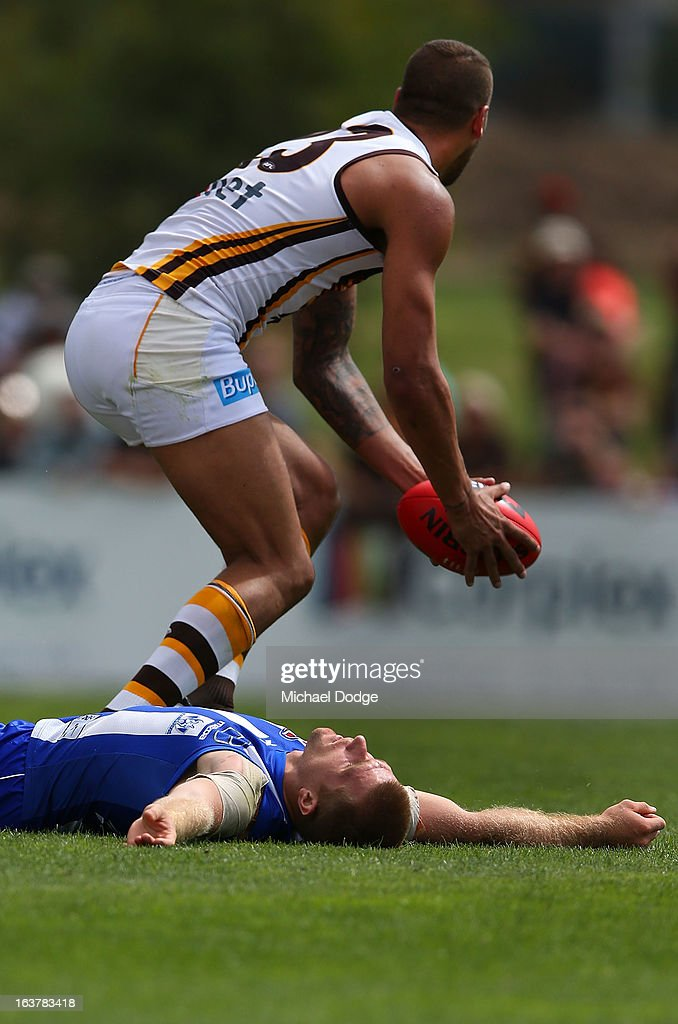 Leigh Adams of the Kangaroos lies on the ground after getting hit in the head by <a gi-track='captionPersonalityLinkClicked' href=/galleries/search?phrase=David+Hale+-+Australian+Rules+Footballer&family=editorial&specificpeople=15090028 ng-click='$event.stopPropagation()'>David Hale</a> of the Hawks when contesting for the ball during the AFL NAB Cup match between the North Melbourne Kangaroos and the Hawthorn Hawks at Highgate Recreational Reserve on March 16, 2013 in Craigieburn, Australia.