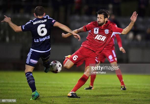 Leigh Broxham of the Victory competes for the ball with Vince Lia of United during the round of 16 FFA Cup match between Adelaide United and...