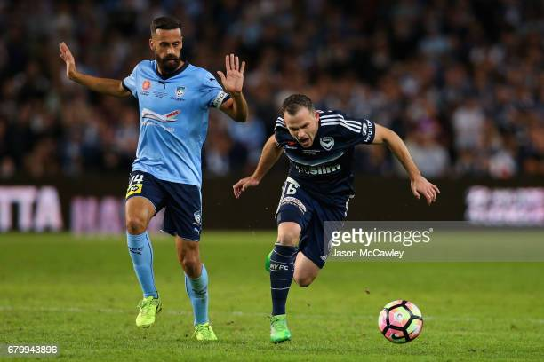 Leigh Broxham of the Victory is challenged by Alex Brosque of Sydney during the 2017 ALeague Grand Final match between Sydney FC and the Melbourne...
