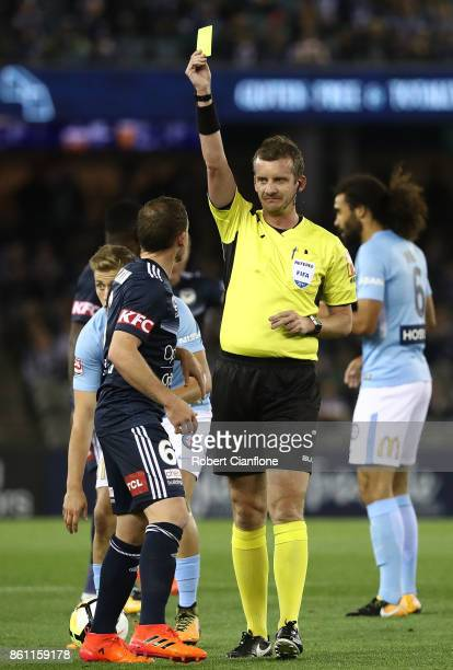 Leigh Broxham of the Victory is shown the yellow card by referee Peter Green during the round two ALeague match between Melbourne Victory and...